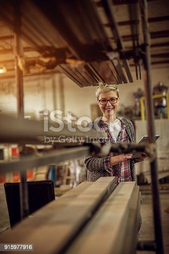 915900234istockphoto Hardworking professional manager happy short hair woman standing behind a row of metal pipes with a tablet in the workshop. 915977916