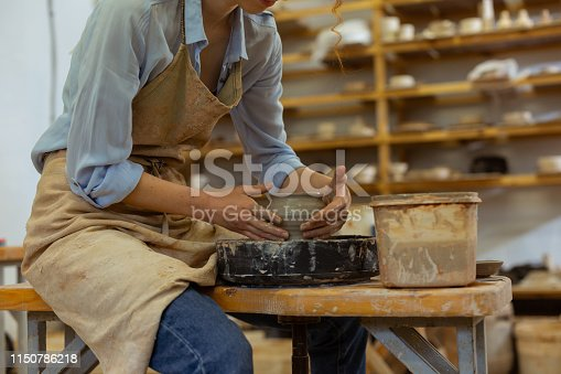 Manufacturing new pot. Hard-working skinny girl showing her experience in pottery while producing tall deep pot