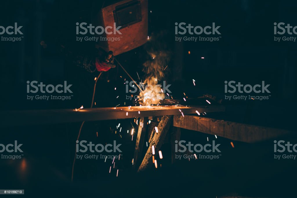 One man, doing his welding work alone, sparks and smoke all around.
