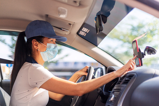 Asian female Car sharing driver checking on the mobilephone searching for job destination, woman wearing face mask while driving