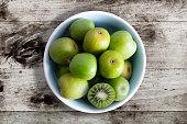 hardy kiwi fruits or kiwi berry Actinidia Arguta in ceramic bowl on wooden kitchen table