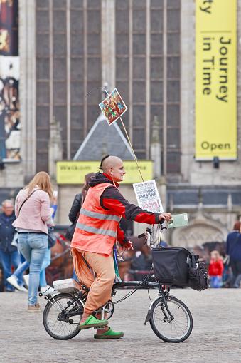 Hare Krishna follower with propaganda material on Amsterdam Dam Square