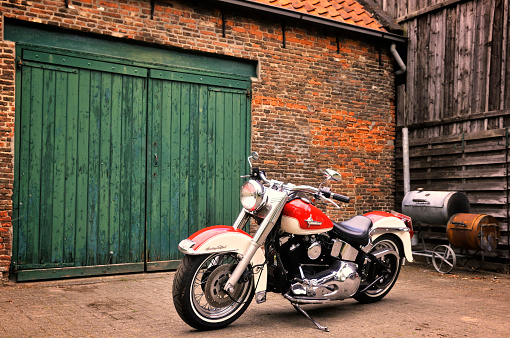 Kampen, The Netherlands - May 13, 2012: 1992 Harley Davidson Heritage Softail motorcycle in front of a barn.