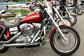 Greenwood Lake New York, USA - June 26, 2016: Harley Davidson Super Glide parked first in a row of Harleys with small boats in the background,  lakeside at this biker handout. Adult toys abound at this location.