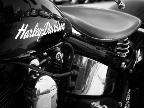 Padua, Italy - May 12, 2012: Harley-Davidson brand name on a motorcycle gas tank. Harley-Davidson Harley-Davidson, also known as H-D or Harley, is an American motorcycle manufacturer founded in Milwaukee during the early 1900. H-D sells heavyweight motorcycles well known all over the world, for their distinctive design and exhaust note. Shot in a public parking.