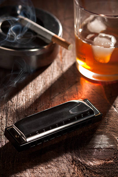 Harmonica with Whiskey and Cigarette stock photo