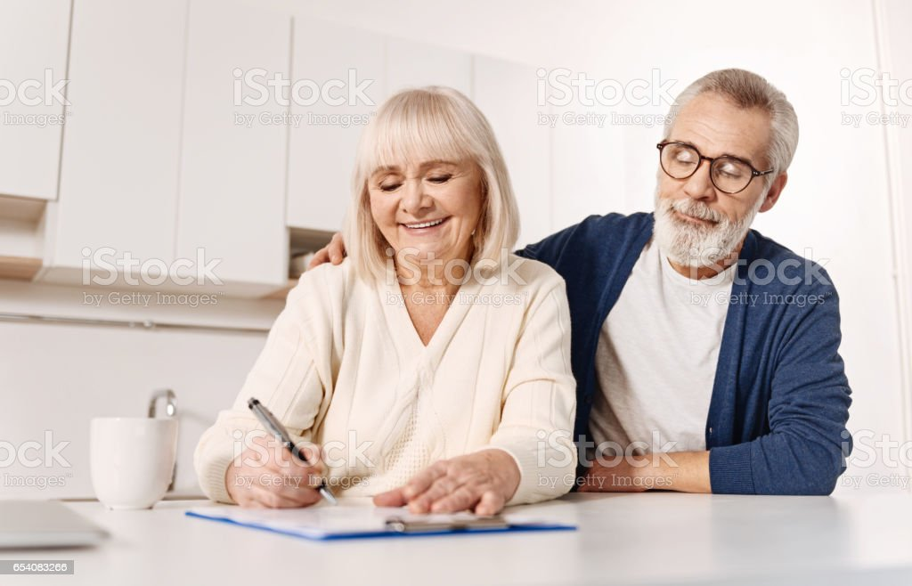 Harmonious aged couple signing documents at home stock photo
