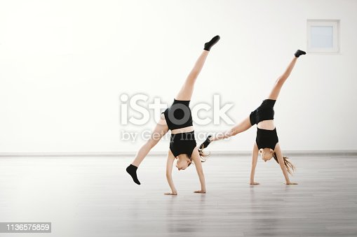 Young dancers doing cartwheel together at dance class.