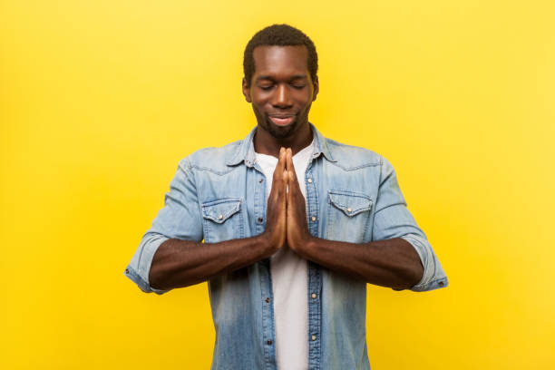 Harmony and relaxation. Portrait of peaceful young man holding arms in namaste. indoor studio shot isolated on yellow Harmony and relaxation. Portrait of peaceful young man in denim casual shirt holding arms in namaste, meditating with closed eyes and grateful calm expression. indoor studio shot isolated on yellow yogi stock pictures, royalty-free photos & images