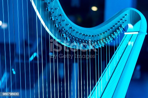 A beautiful harp on display, bathed by a blue neon light.