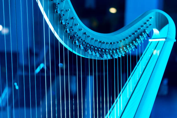 a harp bathed in blue neon light, waiting for an artist. detail of a musical instrument. - harpist stock photos and pictures
