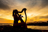 Harp musician on sunset with harp at the seaside.