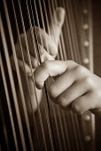 """Hands Playing a Harp, selective focus"""