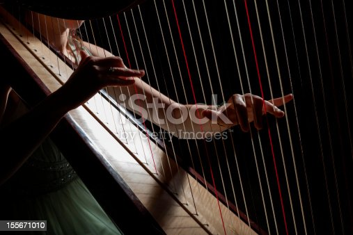 girl is playing harp in darknes