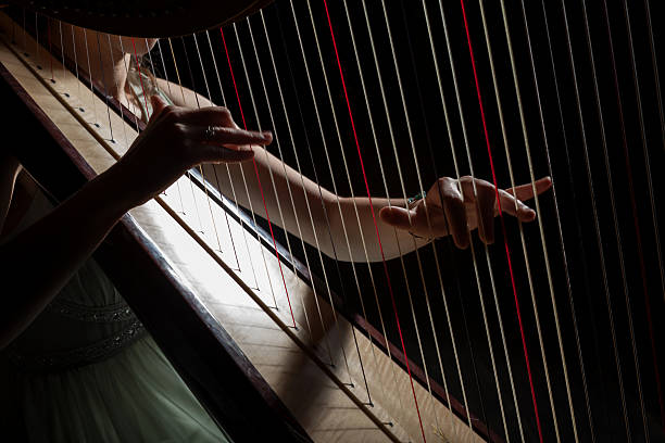 Harp player girl is playing harp in darknes string instrument stock pictures, royalty-free photos & images