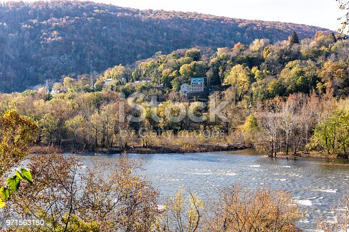 Harper's Ferry blue Potomac River riverside with colorful orange yellow foliage fall autumn by small village town in West Virginia, WV, house on hill mountain