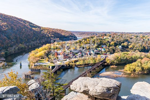 Harper's Ferry overlook closeup of cityscape with cliffs rocks, colorful orange yellow foliage fall autumn forest with small village town by river in West Virginia, WV
