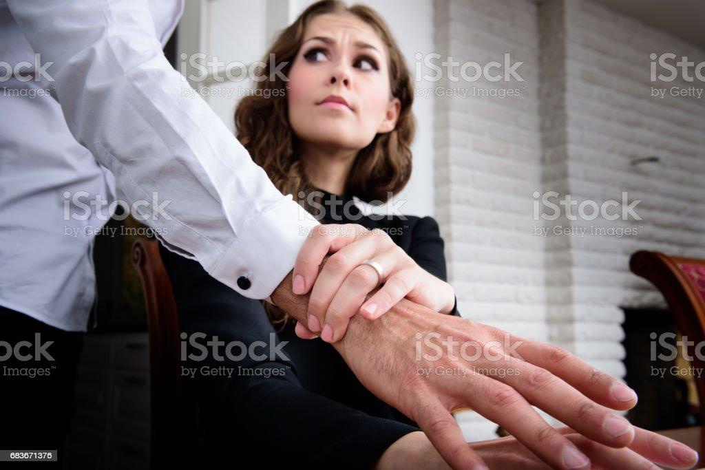 Harrassed woman dislikes his hand stock photo