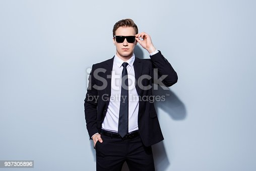 973213156 istock photo Harsh agent, standing on a pure background. He looks stunning and severe, wearing suit and sunglasses, fixing them and has a hand in a pocket 937305896