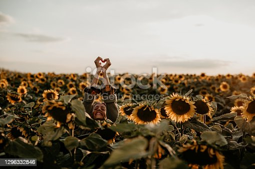 Smiling female in a green outfit standing and showing hart shape in the sunflower field. Lifestyle nature concept.