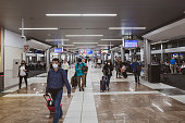 Atlanta, USA - March 21, 2020: Passengers at Hartsfield-Jackson Atlanta International Airport walk inside a terminal. On account of the ongoing coronavirus pandemic, many passengers wear a respirator mask for protection.