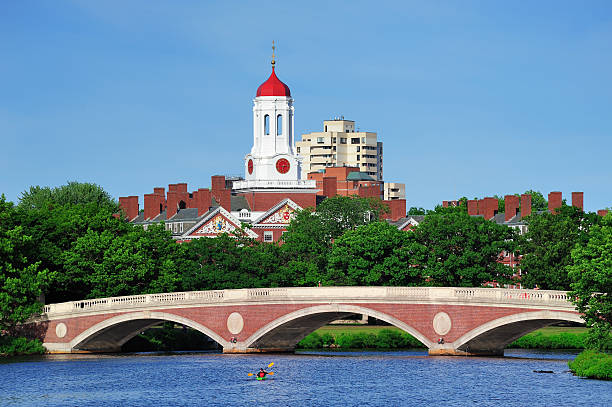 Harvard campus in Boston John W. Weeks Bridge and clock tower over Charles River in Harvard University campus in Boston with trees, boat and blue sky. harvard university stock pictures, royalty-free photos & images
