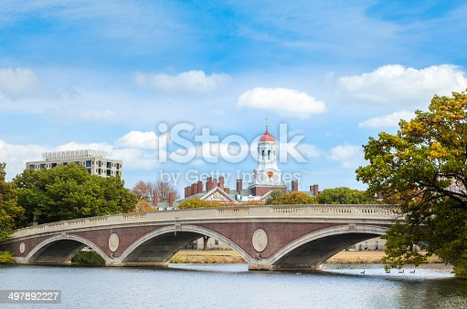 A brick and concrete three-span arch-style footbridge, the John W. Weeks Bridge spans the Charles River near Harvard University in Cambridge, Massachusetts. The red-capped white central tower of Harvard's Dunster House stands tall amid puffy white clouds, while trees grace either end of the bridge.