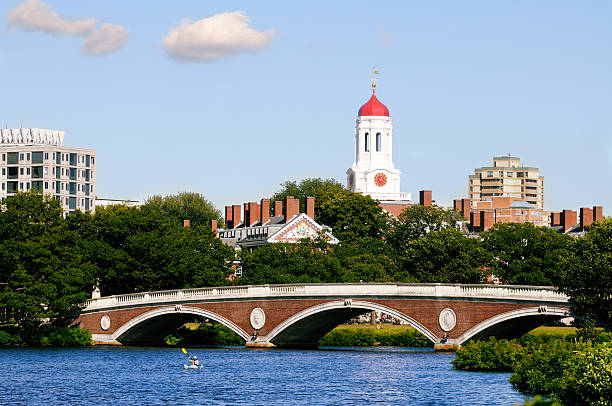 Harvard University View of Harvard University and pedestrian bridge on Charles River in Cambridge, Massachusetts footbridge stock pictures, royalty-free photos & images