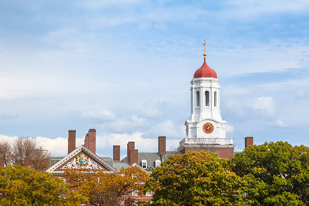 harvard university's dunster house central tower rises above autumn foliage - harvard university stock photos and pictures