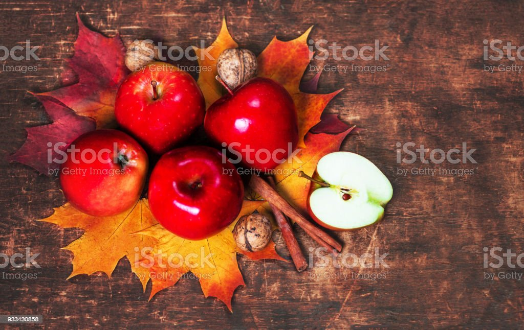 Harvest Background with red ripe apples and marple leaves on wooden table with copy space. Seasonal autumnal concept stock photo