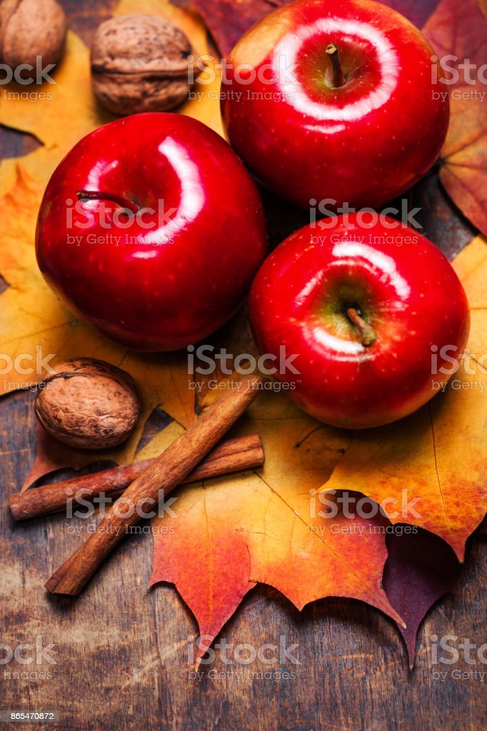Harvest Background with red ripe apples, cinnamon sticks  and marple leaves on wooden table with copy space. Thanksgiving day or seasonal autumnal concept stock photo