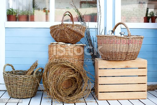 Harvest concept. Harvesting autumn crops in baskets. Wicker baskets against the wall of a blue country house. rustic style. Gardening. Autumn harvest of plenty. Gardening concept. Vegetable