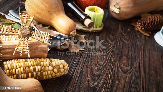 Happy Thanksgiving Day background, wooden table decorated with pumpkins, wine, corncob, candles and autumn leaves. The concept of harvest and autumn celebration.
