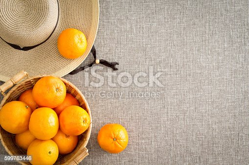 istock Harvest of farm fresh oranges with a straw sunhat 599763446