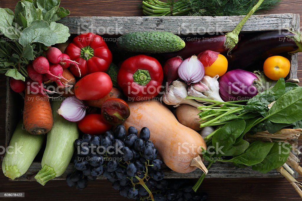Harvest of veggies in wood box top view stock photo