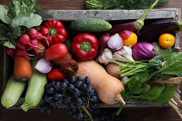Harvest of veggies in wood box top view stock photo