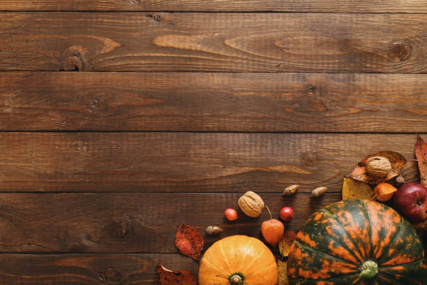 Harvest or Thanksgiving background with pumpkins, dried fall leaves, apples, red berries, walnuts on wooden table. Flat lay composition, top view, copy space