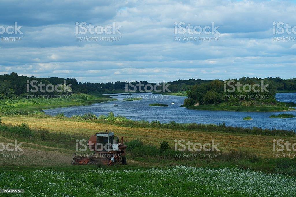 Harvester harvests near river stock photo