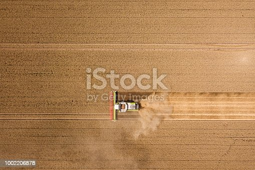 istock Harvester harvests wheat on a field, Thuringia, Germany 1002206878