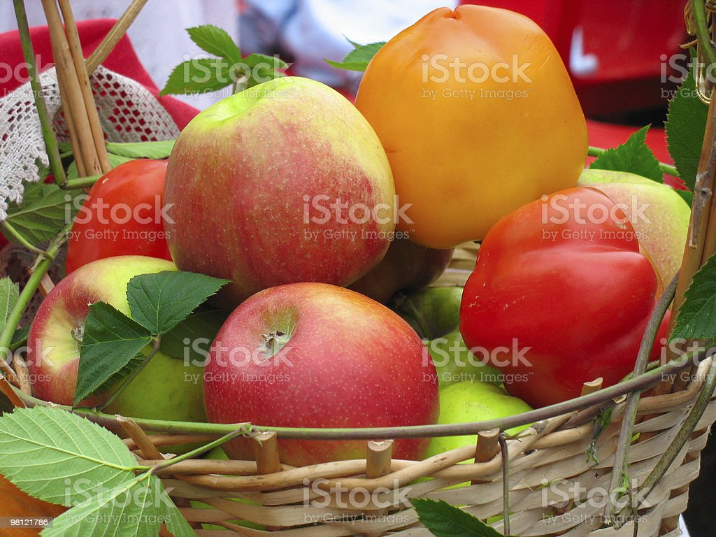 Harvesting apples, leaves and sweet peppers in wooden basket royalty-free stock photo