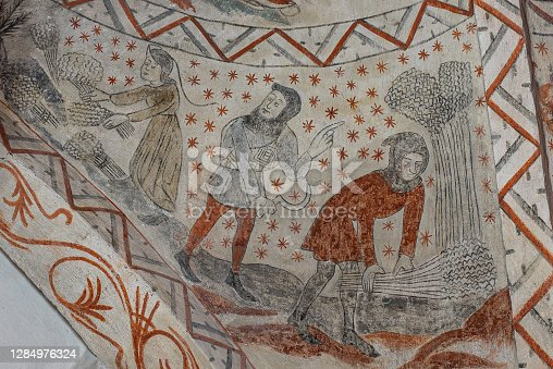 istock harvesting the self-growing corn, a medieval legend on a wall-painting in Tuse c 1284976324