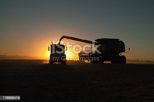 A combine,or harvester, silhouetted in the sunset, dumps soybeans into a semi tractor-trailer in a dusty soybean field
