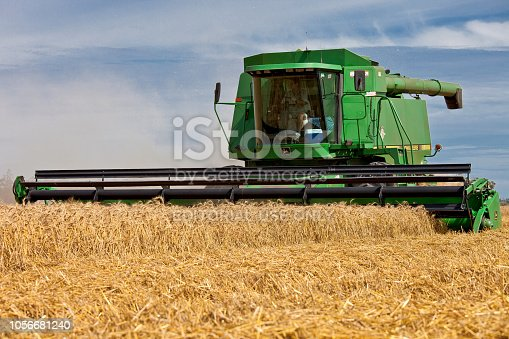 Moree, Australia - November 22, 2010: A combine harvester harvests wheat on a large grain farm in Moree. This is a major agricultural area in New South Wales, Australia.