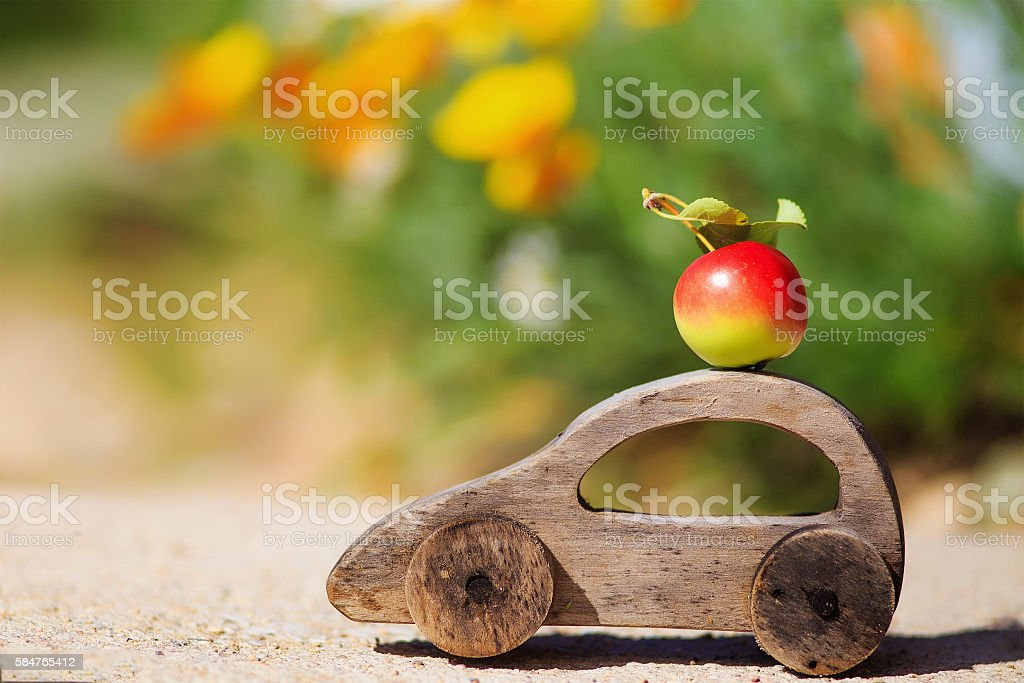 harvesting. wooden toy car with an apple stock photo