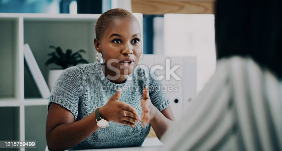 Shot of a young businesswoman having a discussion with a colleague in an office