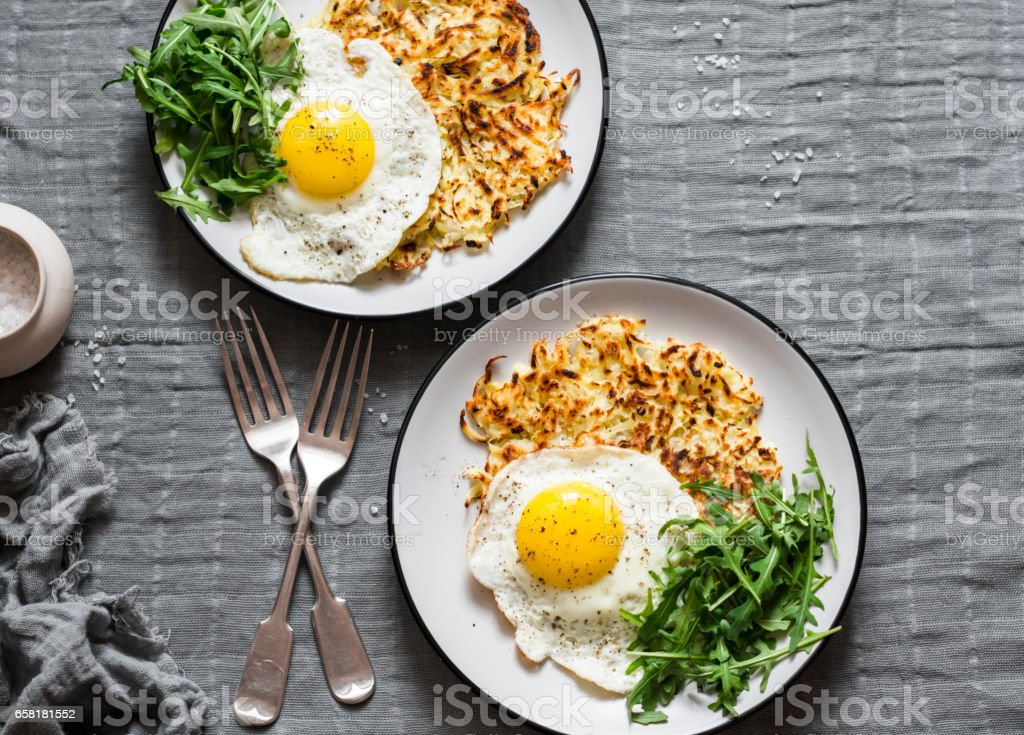 Hash Browns, fried egg and arugula on grey background, top view. Delicious simple lunch stock photo