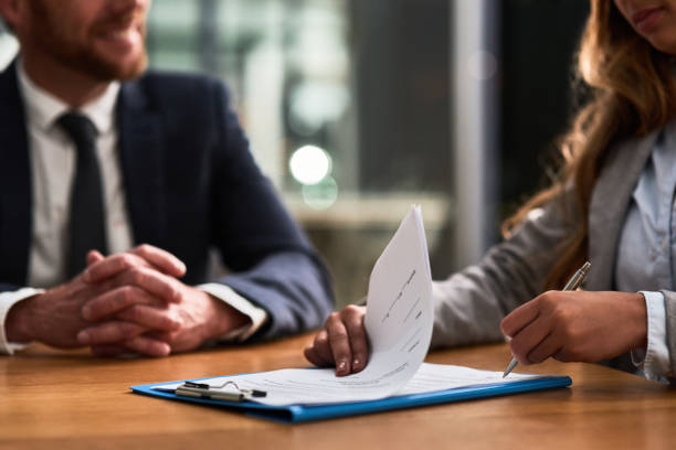 Hashing out the terms and conditions of the contract Cropped shot of a businessman and businesswoman completing paperwork together at a desk signing stock pictures, royalty-free photos & images