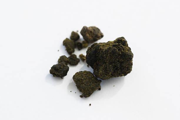 hashish pieces on white background macro stock photo