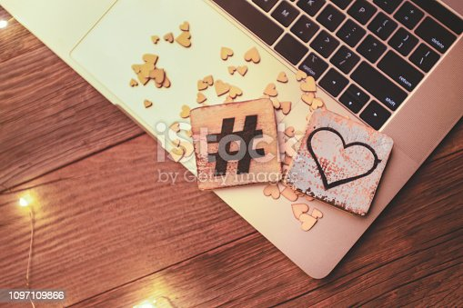 Hashtag Love heart on a computer with a wood background. Internet dating concept.