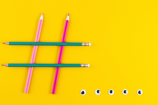 1125605742 istock photo Hashtag sign from crossed colorful pencils on yellow background. 1256705107